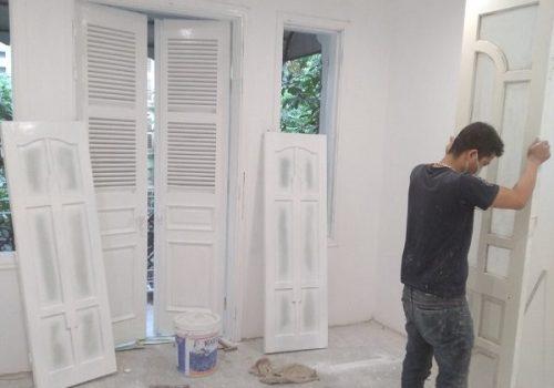 Thợ sơn cửa gỗ màu trắng tại Triệu Việt Vương, Bùi Thị Xuân, Hà Nội